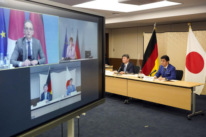 """Japanese Foreign Minister Toshimitsu Motegi, second from right, and Defense Minister Nobuo Kishi, right, attend a video conference with German Foreign Minister Heiko Maas, top left on screen, and German Defense Minister Annegret Kramp-Karrenbauer, top right on screen, at Foreign Ministry in Tokyo during their """"2 plus 2"""" ministerial meeting Tuesday, April 13, 2021. (Frank Robichon/Pool Photo via AP)"""