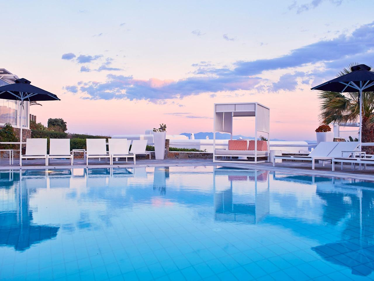 """Less than a quarter mile from the golden-sand Kalo Livadi beach, one of the longest on <a href=""""https://www.cntraveler.com/gallery/reasons-to-visit-the-greek-islands?mbid=synd_yahoo_rss"""">Mykonos</a>, the Archipelagos Hotel is about as idyll a retreat as you'll find, despite sitting on one of Greece's more popular spits of land. Take in a Cycladean sunset from your post on the pool deck, or, if you prefer, from the comfort of your room—designed like an amphitheater, many of the set-ups offer views of the region's azure waters. Come breakfast, stake out the buffet, a princely spread of fresh pastries, breads, meats, cheeses, and dried fruit to sustain you for the day ahead—whether that means a hike up the isle's rocky crags, or one parsing past issues of <em>The New Yorker</em> by the pool."""