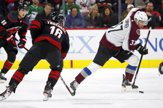 Colorado Avalanche's J.T. Compher (37) skates with the puck away from Carolina Hurricanes' Vincent Trocheck (16) during the first period of an NHL hockey game in Raleigh, N.C., Friday, Feb. 28, 2020. (AP Photo/Karl B DeBlaker)