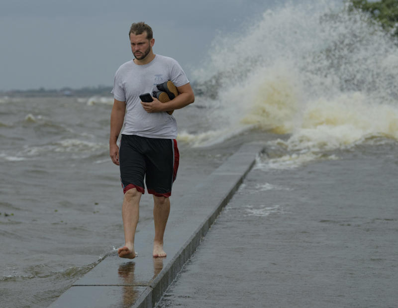 Wesley Vinson wades through storm surge from Lake Pontchartrain on Lakeshore Drive in Mandeville, La., as Hurricane Barry approaches Saturday, July 13, 2019. (Photo: Matthew Hinton/AP)