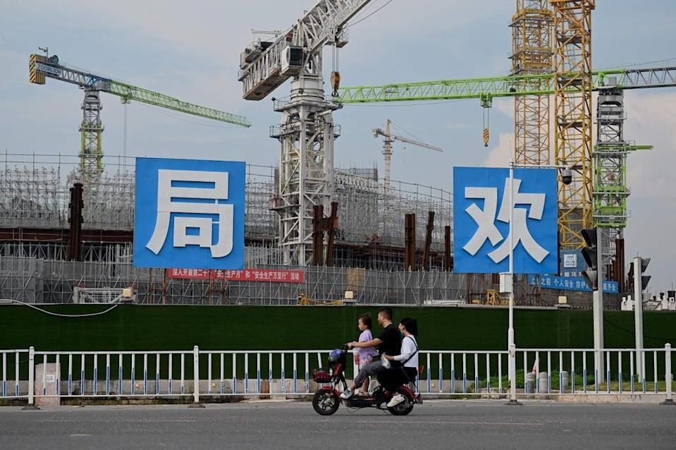 People commute in front of the under-construction Guangzhou Evergrande football stadium in Guangzhou, China's southern Guangdong province  (AFP via Getty Images)
