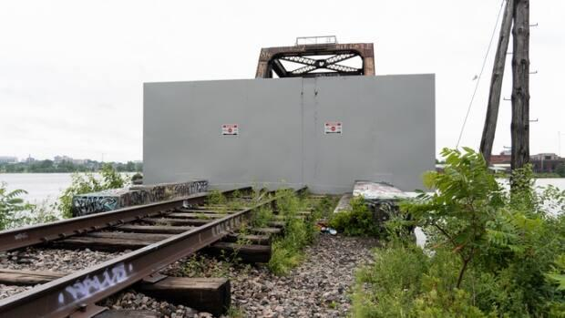 A recently installed metal barrier is seen on the Gatineau, Que., side of the Prince of Wales Bridge on June 26, 2021. Earlier this month, a 26-year-old man drowned after jumping off the Ottawa side of the decommissioned rail bridge.  (Alexander Behne/Radio-Canada - image credit)