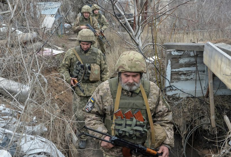 FILE PHOTO: Service members of the Ukrainian armed forces walk at fighting positions near Donetsk