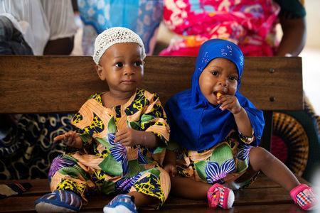 Non-identical twins Kehinde Akinbola and Taiwo Akinbola snack while waiting to receive their immunisations at the hospital in Igbo Ora, Oyo State, Nigeria April 4, 2019. PIcture taken April 4, 2019. REUTERS/Afolabi Sotunde