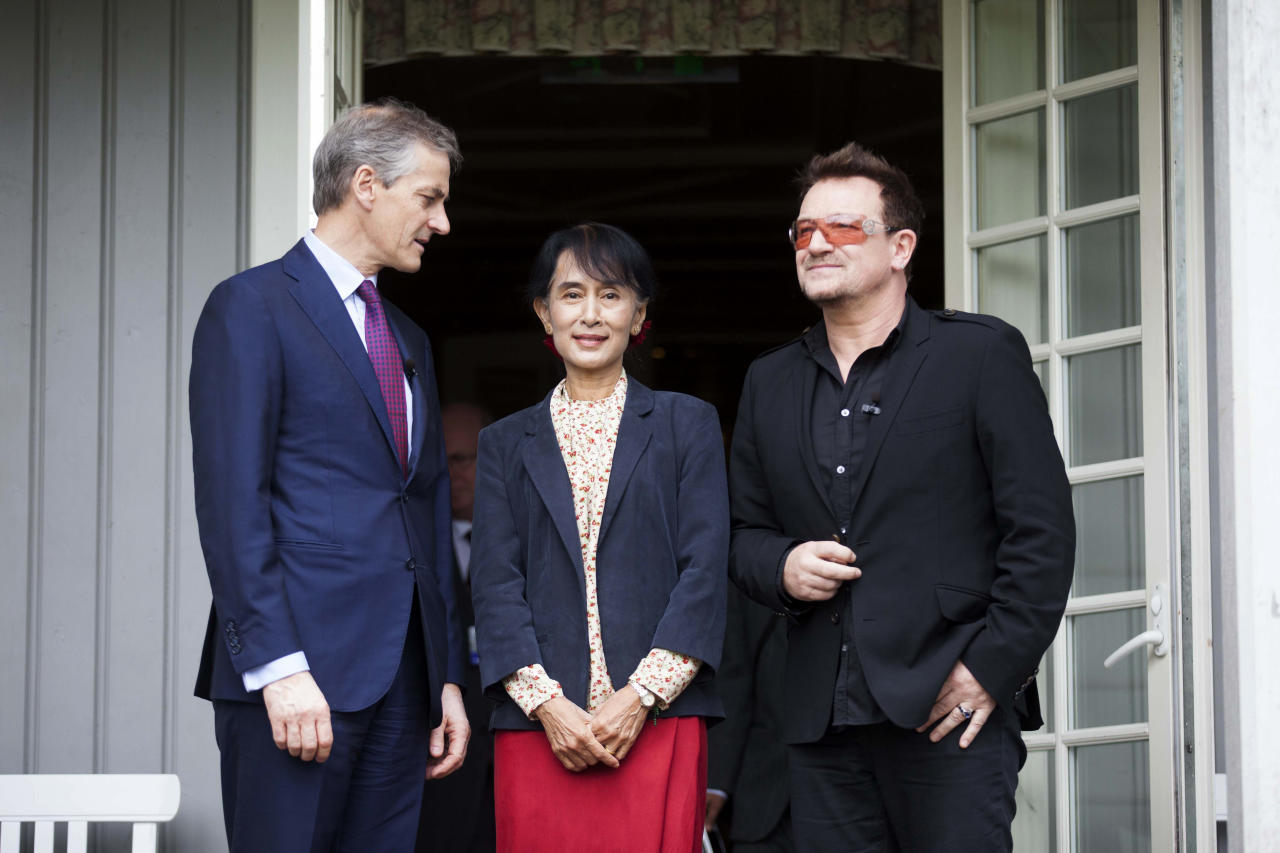 From left, Norwegian Foreign Minister Jonas Gahr Stoere, Myanmar opposition leader Aung San Suu Kyi and Irish singer and activist Bono pose for the media after they attending a conference of the Oslo Forum at the Losby Gods resort, about 13 kilometers (8 miles) east of Oslo, Monday, June 18, 2012. The Oslo Forum is a n international network of armed conflict mediation practitioners. (AP Photo/Markus Schreiber)