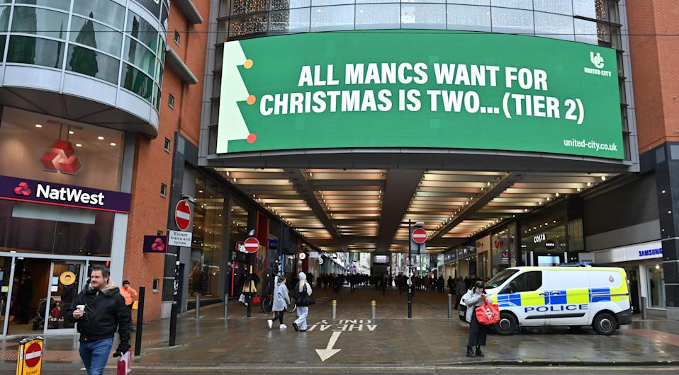 "Pedestrians walk beneath a sign reading ""All Mancs Want For Christmas Is Two... (Tier2)"", referring to manchester's current Tier 3 COVID-19 statues, in Manchester, northern England on December 2, 2020 as England emerges from a month-long lockdown to combat the spread of Covid-19. - England on December 2 exited a month-long lockdown into a new 3-tiered system of curbs with non-essential retail, leisure centres and salons all reopening but with some sectors, including hospitality, seeing tighter restrictions. (Photo by Paul ELLIS / AFP) (Photo by PAUL ELLIS/AFP via Getty Images)"