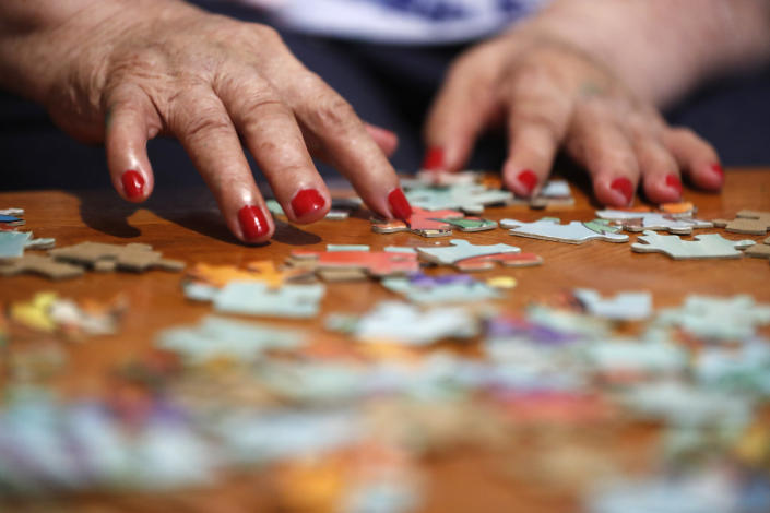 Francisca Perez, 84, rearranges puzzle pieces, a part of her regular exercise to recover from rheumatoid arthritis, Wednesday, June 30, 2021, in Chicago's Little Village neighborhood. She suffers from a heart condition and depression, among other ailments. Her daughter, Eugenia Rodriguez, hasn't been eligible for insurance coverage after overstaying a visitor visa from Mexico. She used to wake up every two or three hours at night to check on her mother. Since getting health insurance through the Illinois program, her mother has all the medications she needs. (AP Photo/Shafkat Anowar)