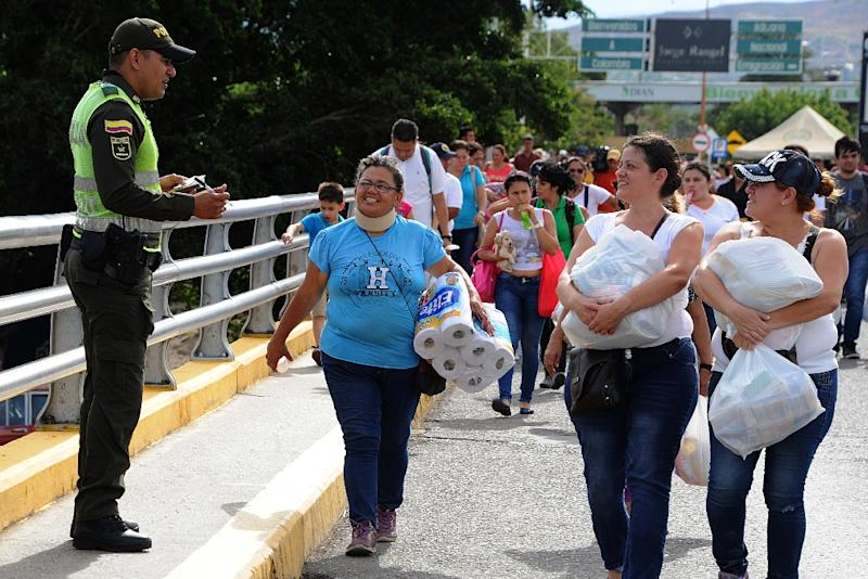 Venezuelans carrying groceries cross the Simon Bolivar bridge from Cucuta in Colombia back to San Antonio de Tachira in Venezuela, on July 10, 2016 (AFP Photo/George Castellanos)