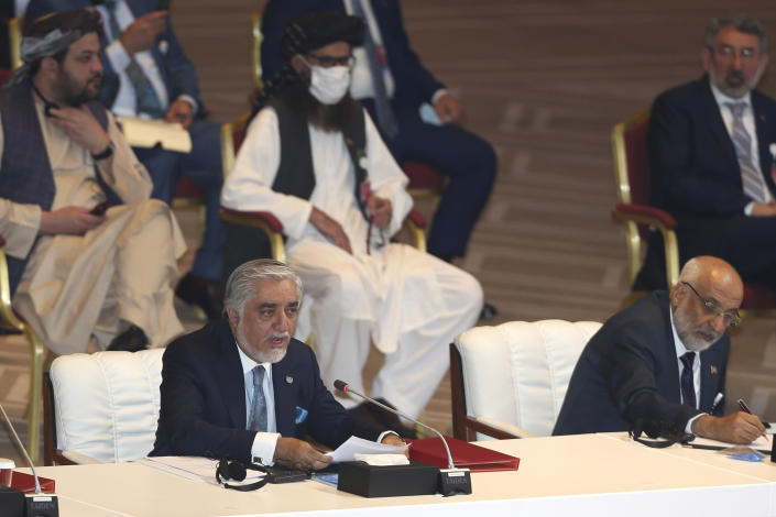 Abdullah Abdullah, left, chairman of Afghanistan's High Council for National Reconciliation, talks at the opening session of the peace talks between the Afghan government and the Taliban in Doha, Qatar, Saturday, Sept. 12, 2020. (AP Photo/ Hussein Sayed)