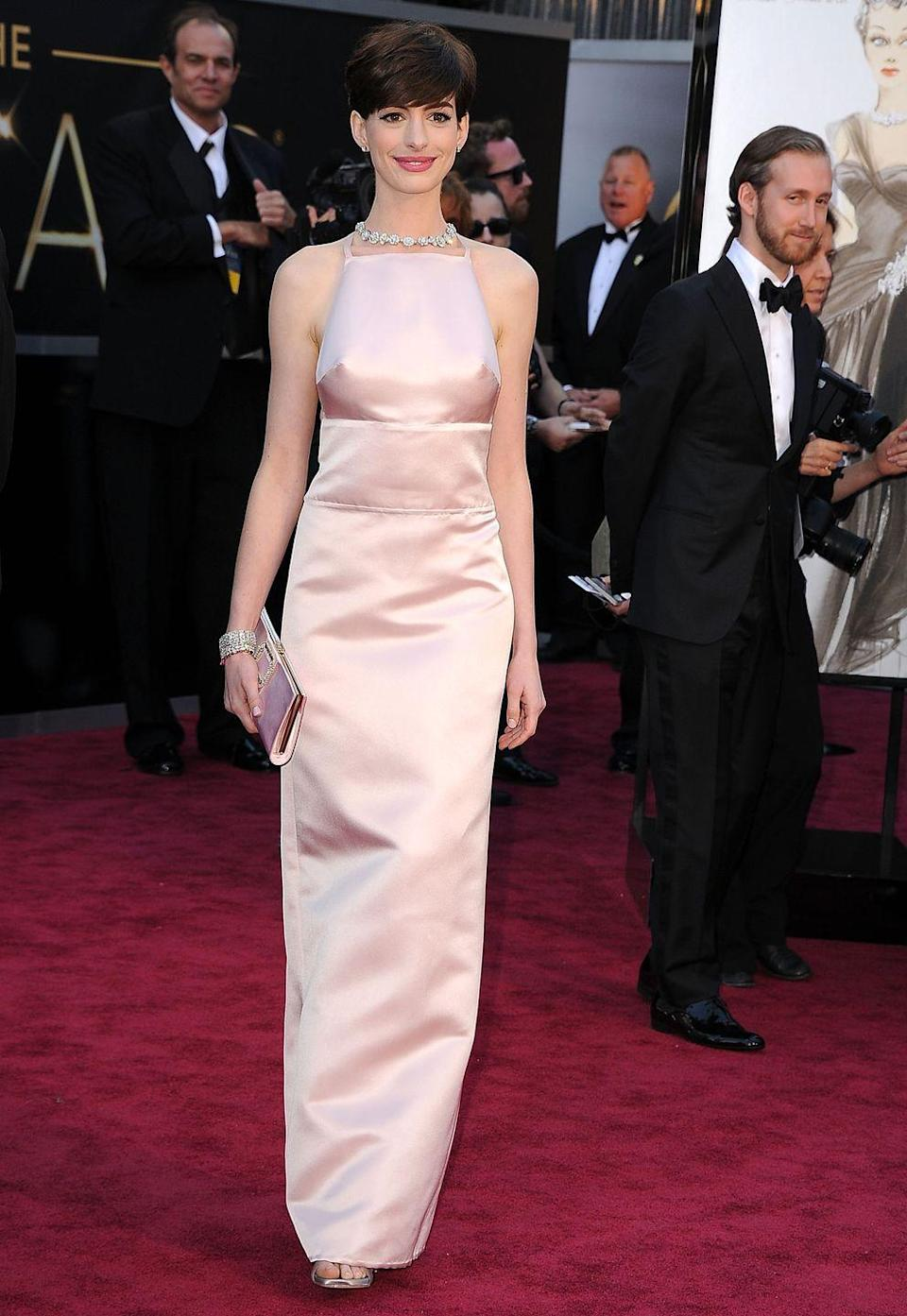 """<p>Critics had a <em>lot </em>to say about this pale pink Prada dress that Anne Hathaway wore to the 2013 Academy Awards. One <a href=""""https://www.hollywood.com/celebrities/anne-hathaway-oscar-dress-worst-dressed-60231127/"""" rel=""""nofollow noopener"""" target=""""_blank"""" data-ylk=""""slk:writer"""" class=""""link rapid-noclick-resp"""">writer</a> called it """"simultaneously bland, confusing, ill-fitting, and vaguely inappropriate."""" Turns out, it <a href=""""https://www.usatoday.com/story/life/entertainthis/2014/10/09/anne-hathaway-finally-explains-that-pink-oscar-dress/77324896/"""" rel=""""nofollow noopener"""" target=""""_blank"""" data-ylk=""""slk:wasn't Anne's first choice either"""" class=""""link rapid-noclick-resp"""">wasn't Anne's first choice either</a>. She had another dress picked out, but found out shortly before the Oscars that her <em>Les Misérables </em>costar Amanda Seyfried was going to wear something almost identical. So she wore this instead, to the horror of fashion bloggers everywhere. </p>"""