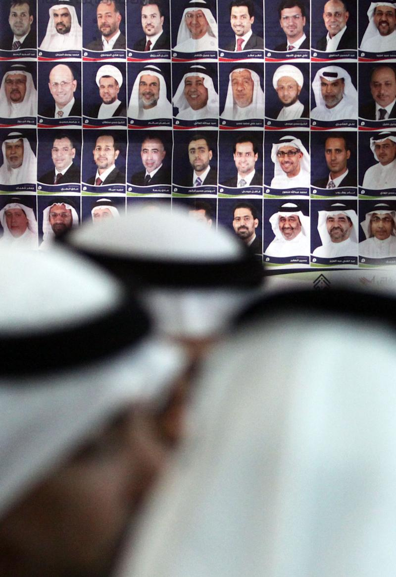 Members of the Shiite opposition al-Wefaq Party gather,  Sunday, Oct. 24, 2010, Manama, Bahrain, headquarters in front of a poster of its candidates who ran in Saturday's elections. Al-Wefaq secured 18 seats in the 40-seat legislature, but party leader Sheik Ali Salman alleged the government's election rules prevent Shiites from obtaining a majority in parliament. (AP Photo/Hasan Jamali)