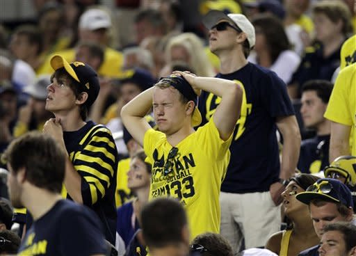 Michigan fans in the stands react to a play during the first half of an NCAA college football game against the Alabama at Cowboys Stadium in Arlington, Texas, Saturday, Sept. 1, 2012.  (AP Photo/LM Otero)