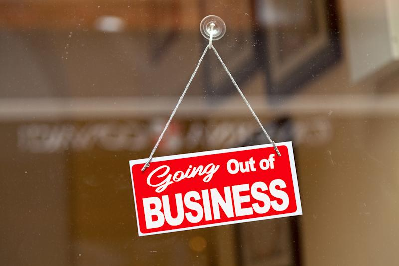 """Red sign hanging at the glass door of a shop saying: """"Going out of business"""". Source: Getty Images"""