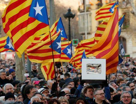 Protestors wave Catalan Estelada flags and hold up a faux ballot box as they await the arrival of former Catalan President Artur Mas outside court in Barcelona