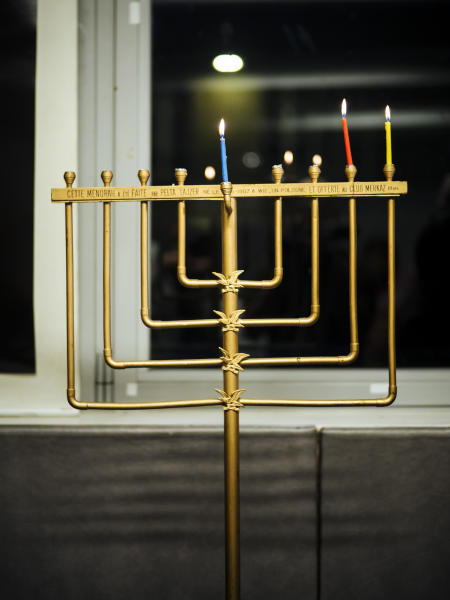 A menorah is seen during an event named 'Survivors Night' in Paris, Monday, Dec. 23, 2019. Holocaust survivors in several cities around the world are lighting candles for Hanukkah together, as Jewish community leaders try to keep first-hand memories of the Nazi horrors alive. The events were organized by the Conference on Jewish Material Claims Against Germany. (AP Photo/Kamil Zihnioglu)