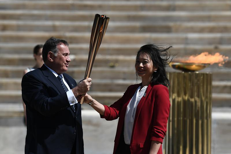 ATHENS, GREECE - MARCH 19: Greek Sports Minister and HOC President Spyros Capralos (L) hands thhe Olympic torch over to former Japanese swimmer Imoto Naoko during the olympic flame handover ceremony for the 2020 Tokyo Summer Olympics, on March 19, 2020 in Athens. The ceremony is held behind closed doors as a preventive measure against the spread of the Covid-19 caused by the novel Coronavirus. (Photo by ARIS MESSINIS / AFP / Pool/Anadolu Agency via Getty Images)