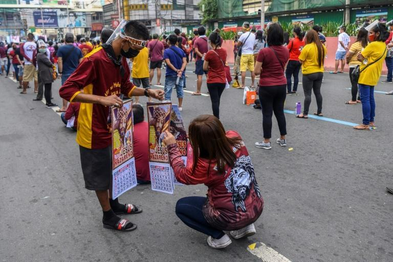 A Catholic devotee buys a calendar with the image of the Black Nazarene during mass on a street in Manila