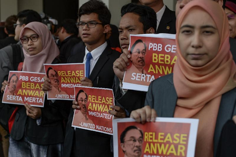 """Members of Malaysian opposition hold placards reading, """"Release Anwar immediately!"""" at Parliament House in Kuala Lumpur, on November 2, 2015 (AFP Photo/Mohd Rasfan)"""