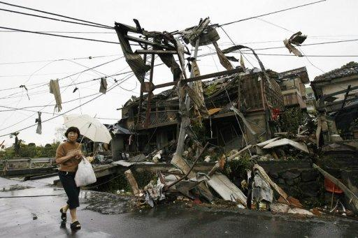 A woman walks past collapsed houses after a tornado swept through a residential area of Tsukuba city in Ibaraki prefecture, north east of Tokyo. Rescue workers rushed 15 people to hospital immediately6 after the tornado