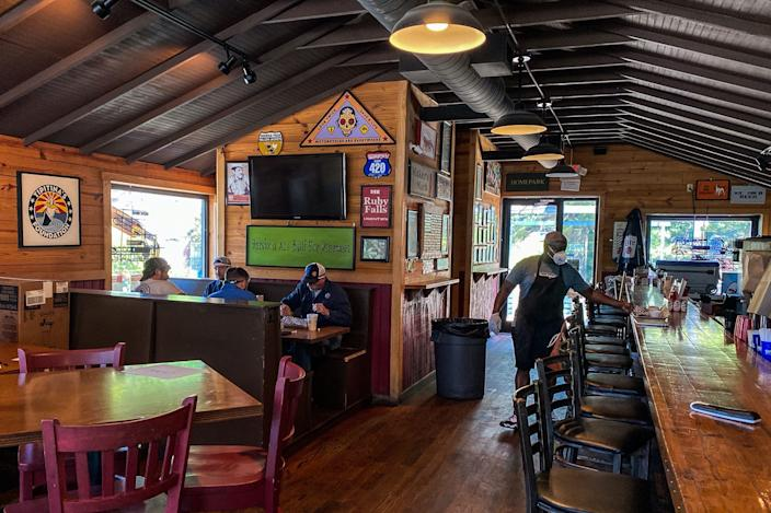 Customers sit and eat at Moe's Original BBQ restaurant in Atlanta, on April 27, 2020. - Some Georgia restaurants reopened on April 27, 2020 for limited dine-in service as the state loosened more coronavirus restrictions.
