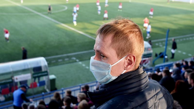 Seen here, a fan in a face mask watches the Belarusian Premier League.