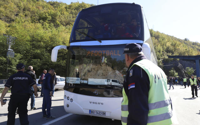 Serbian police officers guard a bus with Red Star players at the border crossing between Serbia and Kosovo, near the village of Rudnica, Serbia, Wednesday, Oct. 9, 2019. Kosovo authorities have banned a soccer match between Red Star Belgrade and a local Serb team and prevented their bus from crossing into the former Serbian province. (AP Photo/Bojan Slavkovic)