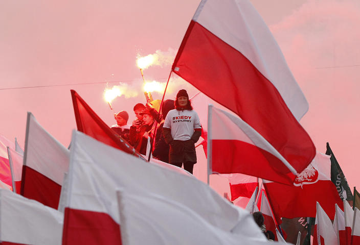 Members of right-wing groups light up flares during a march by some thousands of people, hosted by President Andrzej Duda that marked 100-years since Poland regained independence in Warsaw, Poland, Sunday, Nov. 11, 2018. (AP Photo/Czarek Sokolowski)