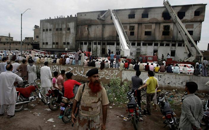 People gather at the site of burnt garment factory in Baldia Town, Karachi, Pakistan on Wednesday, Sept. 12, 2012. Pakistani officials say the death toll from devastating factory fires that broke out in two major cities has risen to 128. Hospital official Tariq Kaleem said the fire at a garment factory in the southern Pakistani city of Karachi killed 103 people. A blaze at a shoe factory in the eastern city of Lahore killed 25 people. (AP Photo/Fareed Khan) - AP Photo/Fareed Khan