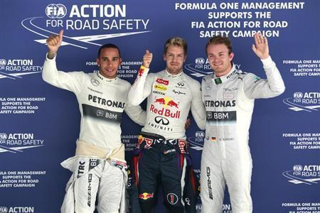 (L-R) Mercedes Formula One driver Lewis Hamilton of Britain, Red Bull Formula One driver Sebastian Vettel of Germany and Mercedes Formula One driver Nico Rosberg of Germany pose for photographers after the qualifying session of the Indian F1 Grand Prix at the Buddh International Circuit in Greater Noida, on the outskirts of New Delhi, October 26, 2013. REUTERS/Anindito Mukherjee