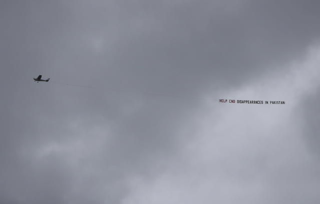 """An aircraft tows a banner that reads """"Help end disappearances in Pakistan"""" as it flies over the venue of the Cricket World Cup semi-final match between England and Australia at Edgbaston in Birmingham, England, Thursday, July 11, 2019. (AP Photo/Aijaz Rahi)"""