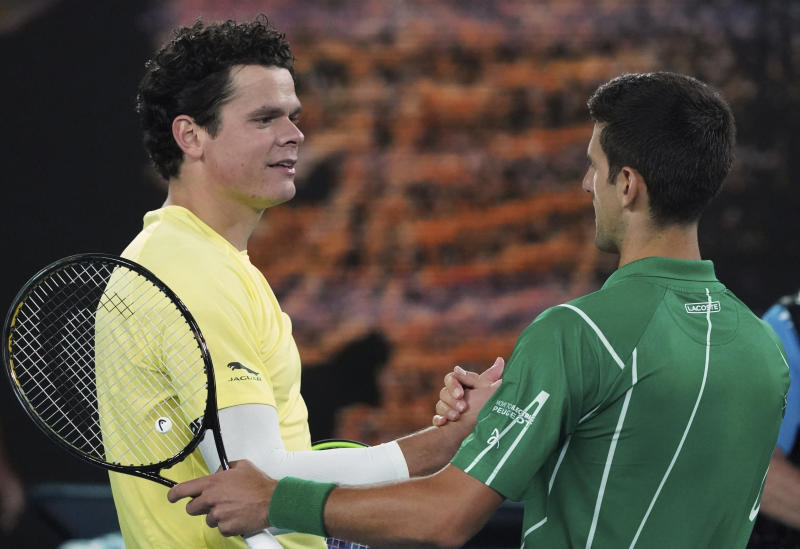 Serbia's Novak Djokovic, right, is congratulated by Canada's Milos Raonic after winning their quarterfinal match at the Australian Open tennis championship in Melbourne, Australia, Tuesday, Jan. 28, 2020. (AP Photo/Lee Jin-man)