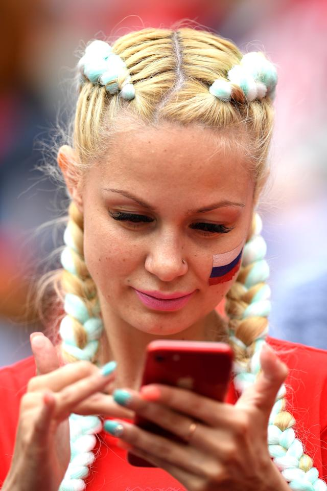 <p>A Russian fan looks at her smartphone prior to the 2018 FIFA World Cup Russia Group A match between Russia and Saudi Arabia at Luzhniki Stadium on June 14, 2018 in Moscow, Russia. (Photo by Matthias Hangst/Getty Images) </p>