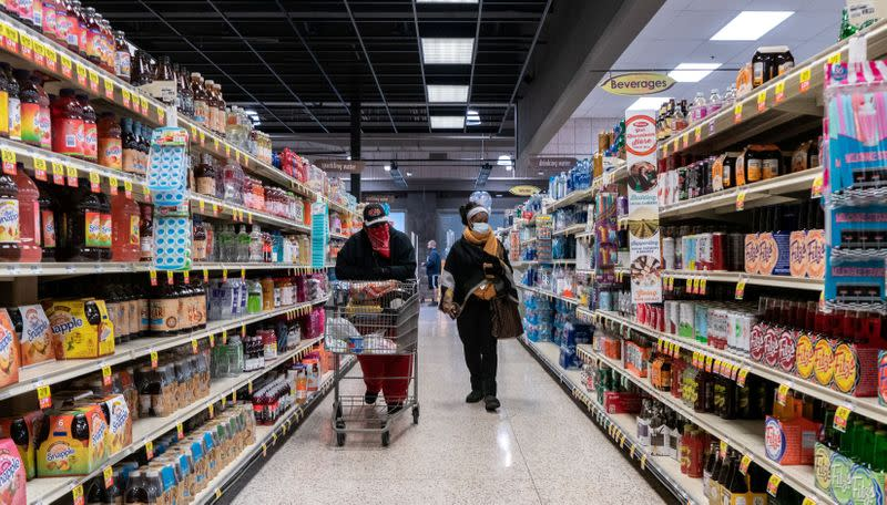 FILE PHOTO: Shoppers browse in a supermarket while wearing masks in St Louis
