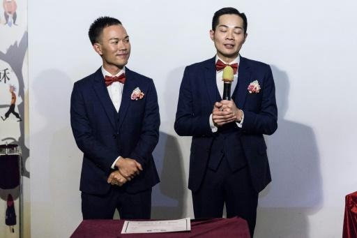 Alvin Chan (L) and C.P. So deliver speeches during their wedding ceremony in Hong Kong, where same-sex unions are not legally recognised and those getting married often say they prefer to do so away from the public gaze