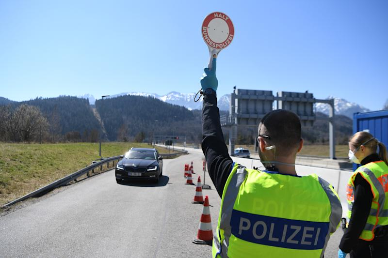 FUSSEN, GERMANY - APRIL 05: A German police man stops a car at a checkpoint at the border to Austria, where crossings have been severely restricted in an effort to rein in the spread of the coronavirus, on April 5, 2020 near Fussen, Germany. Public life in Bavaria remains heavily curtailed with outings limited to essentials as both the state of Bavaria and federal Germany seek to stem the spread of the virus. Nationwide confirmed cases of infection have reached 96,000 and 1,444 people have died. (Photo by Andreas Gebert/Getty Images)