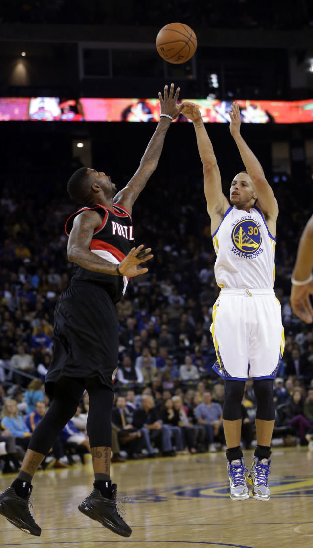 Golden State Warriors' Stephen Curry shoots over Portland Trail Blazers' Dorell Wright during the second half of an NBA preseason basketball game on Thursday, Oct. 24, 2013, in Oakland, Calif. (AP Photo/Marcio Jose Sanchez)