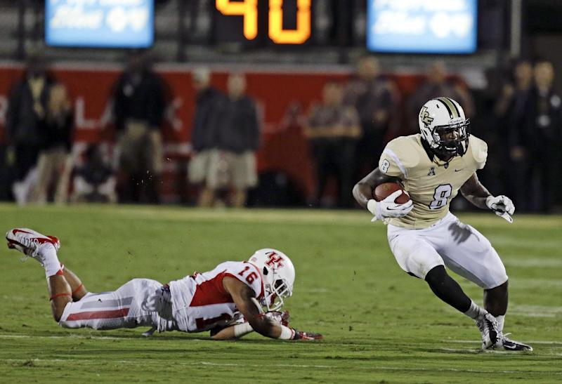Central Florida running back Storm Johnson (8) gains yardage as he gets past Houston's Adrian McDonald (16) during the first half of an NCAA college football game in Orlando, Fla., Saturday, Nov. 9, 2013. (AP Photo/John Raoux)