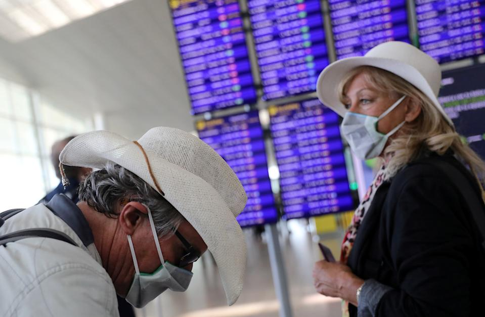 A woman from the Netherlands and her friend from Britain stand next to the display flight information at Josep Tarradellas Barcelona-El Prat Airport, as a case of novel coronavirus has been confirmed in Barcelona, Spain February 26, 2020. REUTERS/Nacho Doce