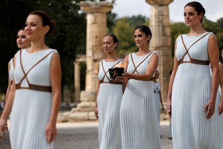 Olympics - Dress Rehearsal - Lighting Ceremony of the Olympic Flame Pyeongchang 2018 - Ancient Olympia, Olympia, Greece - October 23, 2017 Actresses with the flame during the dress rehearsal for the Olympic flame lighting ceremony for the Pyeongchang 2018 Winter Olympic Games at the site of ancient Olympia in Greece REUTERS/Alkis Konstantinidis