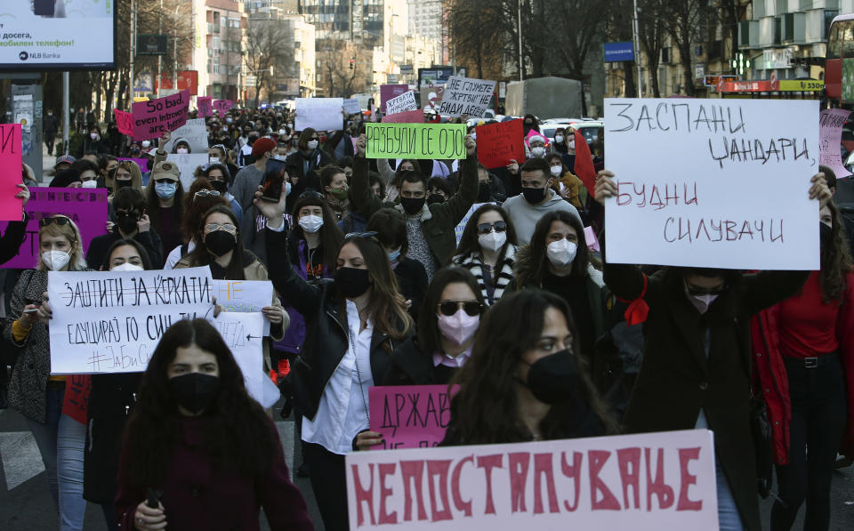 """Young people, wearing face masks and trying to maintain distance, march during a protest through downtown Skopje, North Macedonia, on Wednesday, Feb. 3, 2021. Several hundred mostly young people have gathered in front of the North Macedonia's Interior ministry on Wednesday to protest sexual harassment of women on social media and policy of impunity for that kind of violence. Some of the banners read in Macedonian: """"Cops asleep - Rapists awake"""", Wake up Prosecution"""", """"Protect your daughter, educate your son"""". (AP Photo/Boris Grdanoski)"""
