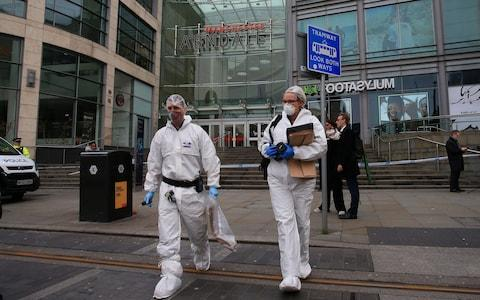 Police forensics officers work outside Arndale Centre shopping complex in Manchester, northwest England on October 11, 2019, following a series of stabbings - Credit: LINDSEY PARNABY/AFP