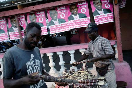 A customer checks sugar cane sold by a street vendor next to posters of presidential candidate Jovenel Moise of PHTK (Bald Head Haitian Party) before the election in a street of Les Cayes