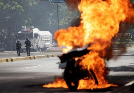Riot security forces look on as a motorcycle bursts into flames during a rally against Venezuela's President Nicolas Maduro's government in Caracas, Venezuela, August 4, 2017. REUTERS/Ueslei Marcelino