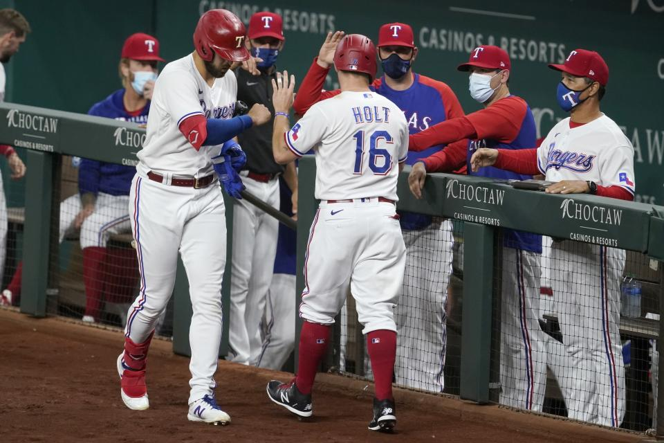 Texas Rangers' Joey Gallo, left, and the dugout celebrate with Brock Holt (16) who scored on a Willie Calhoun single in the second inning of a baseball game against the Los Angeles Angels in Arlington, Texas, Wednesday, April 28, 2021. (AP Photo/Tony Gutierrez)