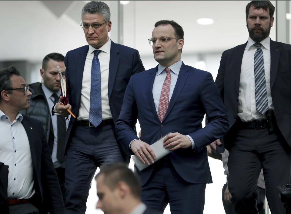 File - In this Thursday, March 26, 2020 file photo, Lothar H. Wieler, president of the Robert-Koch-Institute, top left, and German Health Minister Jens Spahn of the Christian Democratic Union, CDU, party, top center, leave after a press conference in Berlin, Germany, on the fight against the new coronavirus outbreak. German Chancellor Angela Merkel's center-right party, the Christian Democratic Union, CDU, is choosing a new leader on the weekend Saturday Jan. 16 and Sunday Jan. 17, 2021, a decision that will help determine who succeeds Merkel at the helm of the European Union's biggest economy after a 16-year reign. (AP Photo/Michael Sohn, file)