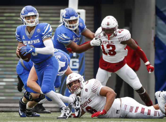 Memphis quarterback Brady White, left, scrambles out of the grasp of Temple defender Daniel Archibong, bottom right, during an NCAA college football game Saturday, Oct. 24, 2020, in Memphis, Tenn. (Mark Weber/Daily Memphian via AP)