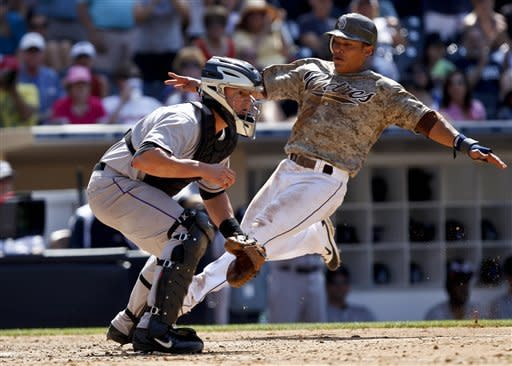 San Diego Padres' Everth Cabrera, right, starts to slide safely into home as Colorado Rockies catcher Jordan Pacheco awaits the late throw during the seventh inning of a baseball game on Sunday, July 22, 2012, in San Diego. Cabrera scored the go-ahead run on a single by John Baker. (AP Photo/Lenny Ignelzi)