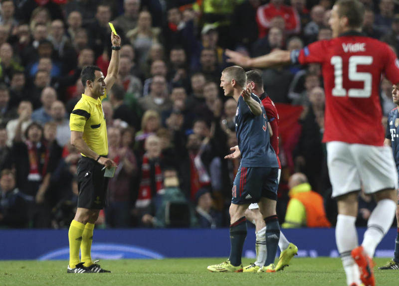Bayern's Bastian Schweinsteiger is booked by referee Carlos Velasco Carballo from Spain, left, during the Champions League quarterfinal first leg soccer match between Manchester United and Bayern Munich at Old Trafford Stadium, Manchester, England, Tuesday, April 1, 2014.(AP Photo/Jon Super)