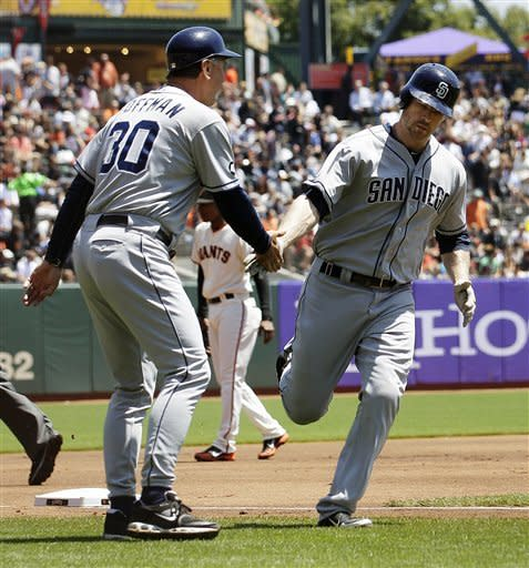 San Diego Padres' Chase Headley, right, is congratulated by third base coach Glenn Hoffman (30) after hitting a solo home run off of San Francisco Giants pitcher Tim Lincecum during the first inning of a baseball game in San Francisco, Wednesday, July 25, 2012. (AP Photo/Jeff Chiu)
