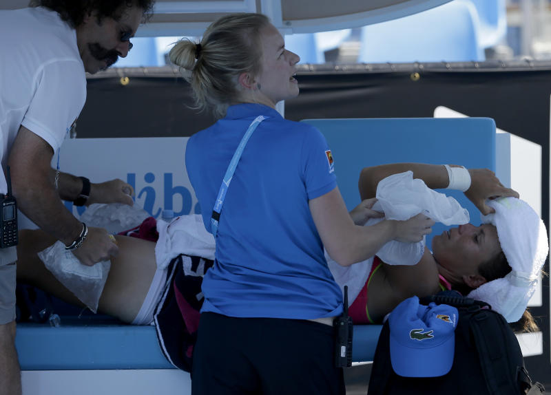 Varvara Lepchenko of the U.S. receives treatment for heat related illness during her second round match against Simona Halep of Romania during her second round match at the Australian Open tennis championship in Melbourne, Australia, Thursday, Jan. 16, 2014. (AP Photo/Aijaz Rahi)